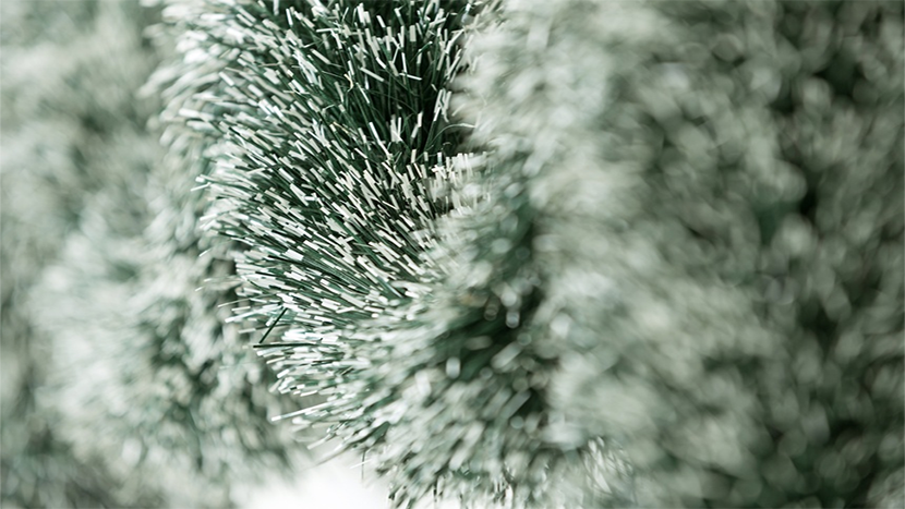 Green Christmas tinsel hanging with snow tipped ends.png